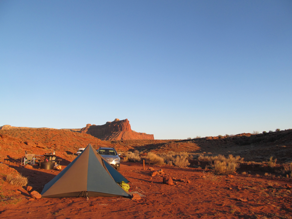 Red Rock, Sunset, Blue/Grey Triangular Tent, Desert, Red Dirt, Blue-ish Sky, No Clouds, Picnic Table.